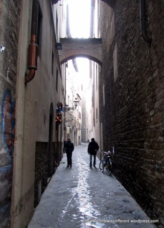 Just an alley with black-clad Florentines and a bike.