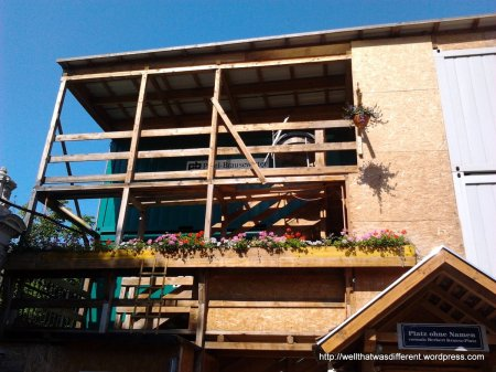 """This is a downtown construction site that has been around for quite a while.  The sign says it is the """"Platz with no name.""""  It has a full complement of window boxes and a little garden out front."""