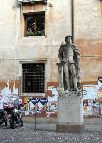 Italy in one photo: statue, stucco, scooter, and graffiti.
