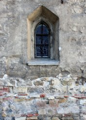Romanesque window and a wall showing the many layers of construction