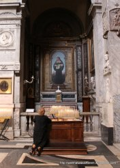 Santa Maria del Popolo: pilgrim praying in a chapel