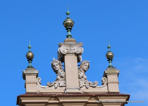 Startled-looking figures on top of the hall.