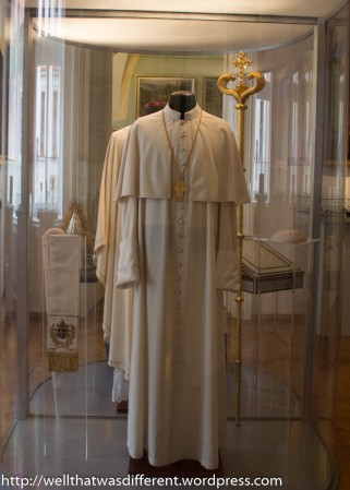 Several papal outfits are on display, along with considerable bling.