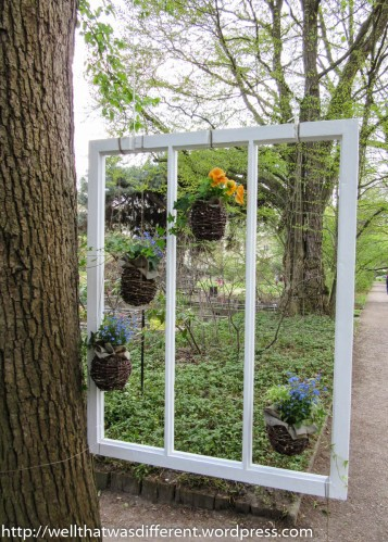 More yard art--an old window frame with hanging plants.