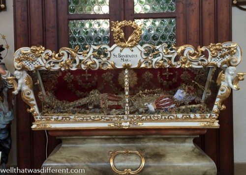 You might be in a former Austrian province if there is a corpse lying resplendent in the church.