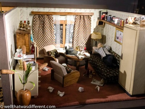 """The """"writers home"""" with discarded pages all over the floor and booze on the table."""